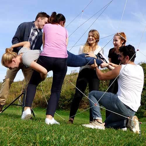 Teilnehmer tragen Kollegin durch das Spider Spiel