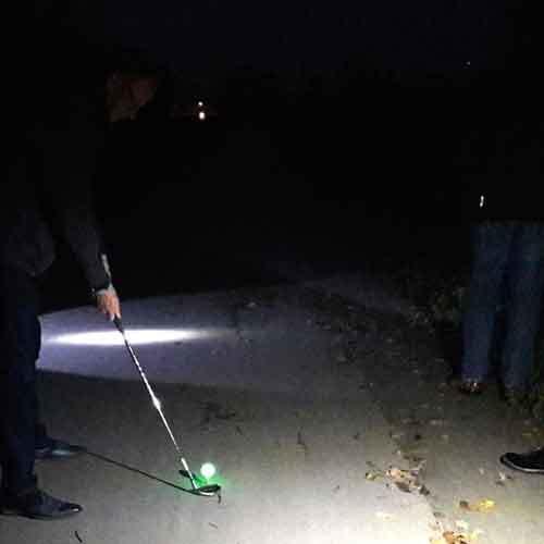 Person beim Crossgolf in Taschanlampenlicht