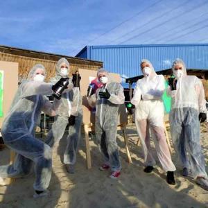 Gruppe mit Spraydosen im Schutzanzug