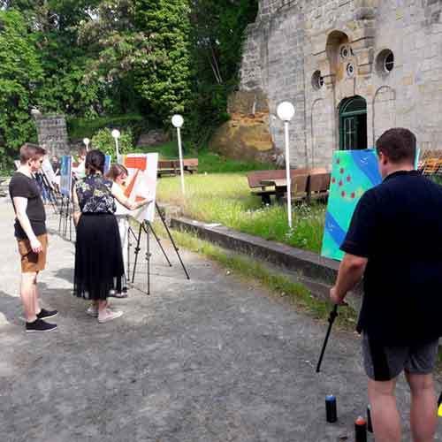 Sprayer vor Staffelei und Historischen Gemäuer