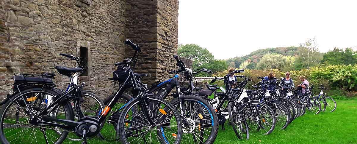 E-Bikes in Reihe vor Historischer Burg